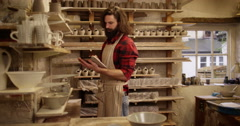 Young attractive man checking stock at a pottery studio on his digital tablet. - stock footage