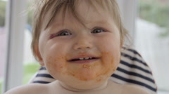 Baby Girl Smiles At Camera Covered In Food Stock Footage
