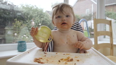 Slow Motion Shot Of Baby Learning To Eat And Gets Covered In Food Stock Footage
