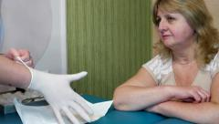 Nurse assistant puts on latex gloves preparing for inspection Stock Footage