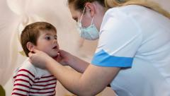 Doctor pediatrician probes the baby's throat knowing the inflammatory process - stock footage