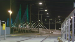 Couple walks across street at public transit station as a trolley crosses bridge - stock footage