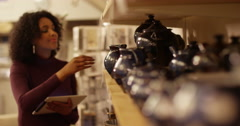 Young woman inspecting quality of the ceramics in her shop. - stock footage