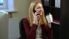 Businesswoman talking on his mobile phone and drinking coffee in the office. 4k Stock Footage