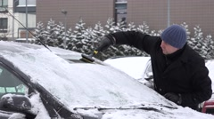 Man with scraper scraping snow and ice from car front window in winter. 4K Stock Footage