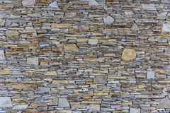 abstraction wall fence built of natural stone background - stock photo