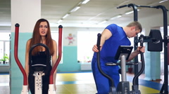 Girl man on simulator sciatica back pain ellipsoid involved with trainer sports Stock Footage
