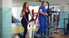 Girl man on simulator ellipsoid involved trainer  sports with Stock Footage