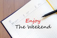 Enjoy the weekend write on notebook - stock photo