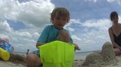 Family Building Sand Castle On Beach Stock Footage