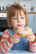 Young Girl Enjoying Eating Sugary Doughnut - stock photo