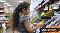 Girl teen in supermarket to buy persimmon fruit food Stock Footage