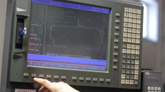 Operator working with control panel of CNC machining centerchanging numbers - stock footage