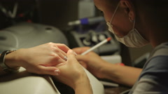 Woman in a nail salon receiving manicure by a beautician. Beauty treatment Stock Footage