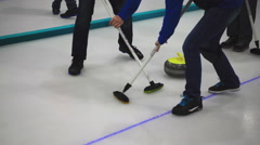 Curling stone slide, players sweeping Stock Footage