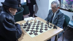 Active Retired Seniors, Two Old Men Playing Chess At old folks club Stock Footage