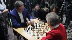 Prime minister of Serbia playing Chess with retiree woman, photographers 2 - stock footage