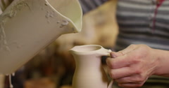 Skilled potter glazing a jug in a ceramic workshop. - stock footage