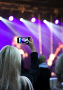 Blond young woman recording stage during concert with cellphone - stock photo