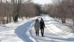 A woman with a girl walking on snow-covered road in winter forest - stock footage
