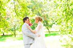 wedding couple hugging, the bride holding a bouquet of flowers in her hand, the - stock photo