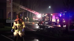 Firetruck With A Ladder And Firefighters Wlaking Through Scene Stock Footage