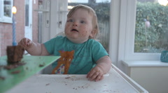 A little girl on her first Birthday blowing out a candle Stock Footage