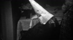 1939: Black dog shamed with newspaper dunce hat timeout. - stock footage