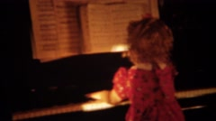 1940: Curly haired girl Shirley Temple clone playing piano. - stock footage