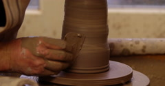 A potter shaping his work on the spinning wheel. - stock footage