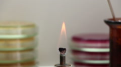 Flame of burner on the petri plates stacks background Stock Footage