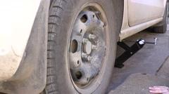 Mechanic Hands Replace Car Tire Outdoor. Closeup. 4K UltraHD, UHD - stock footage