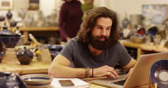 Portrait of an attractive store owner working on his laptop. Slow motion - stock footage