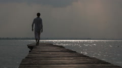 A young man walking along the pier to the sea, Italy - stock footage