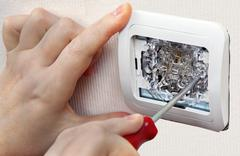 Mount wall light switch, close-up of human hand with screwdriver. Stock Photos