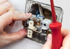 Dismantling and replacing an old, defective wall power switch light. - stock photo