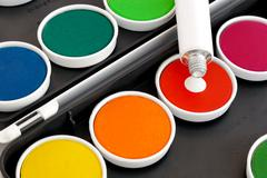 Watercolors with opaque white on black background - stock photo