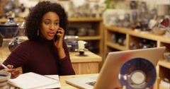 A frustrated African American businesswoman talking on the phone in her shop. - stock footage