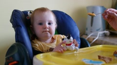 Baby Sits in High Char as Mother Feeds The Child. Baby eats Stock Footage