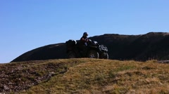 Man driving a quad drive bike (ATV) on a mountain pasture Stock Footage