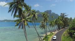 AERIAL: Young woman riding motorbike on beautiful Bora Bora island Stock Footage