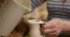 Potter pouring glaze inside jug in a workshop. Slow motion Stock Footage