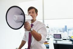 Business Man With Megaphone Doing Announcement In Office - stock photo