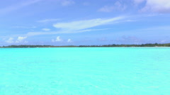 Amazing crystal clear blue lagoon and exotic island on horizon Stock Footage