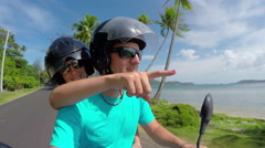 Happy young newlyweds riding Vespa motorbike on Bora Bora honeymoon - stock footage