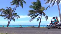 Happy young newlyweds motor biking around Bora Bora island - stock footage