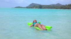 SLOW MOTION: Woman relaxing on water bed floatie in ocean Stock Footage