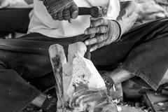 Hand of carver carving wood in black and white color tone - stock photo
