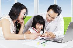 Asian parents teach their daughter to study - stock photo