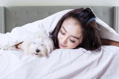 Female model sleeping with dog on bed - stock photo